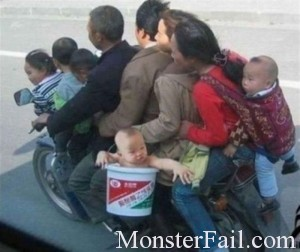 Family of 9 on a motorcycle with a baby in a bucket.