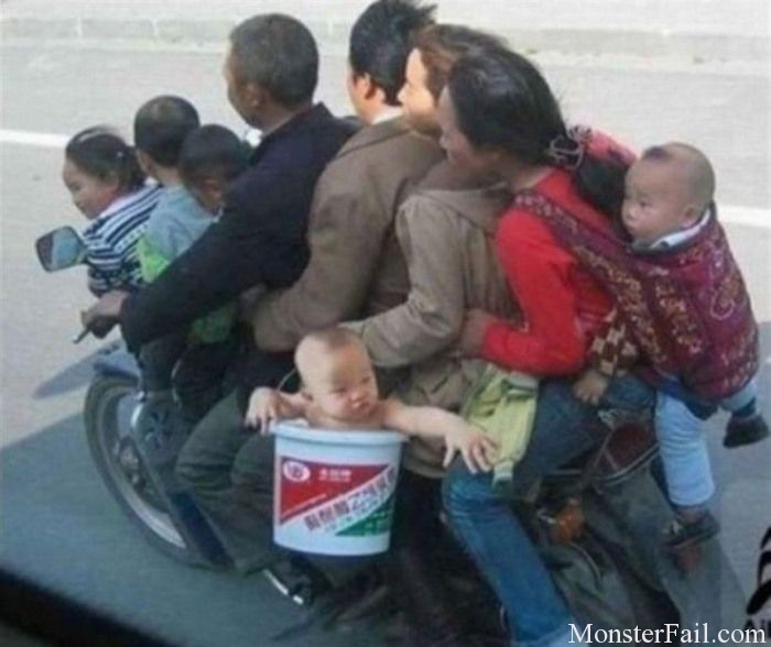 Family of 9 on a single motorcycle with one baby being carried in a 2 gallon bucket.