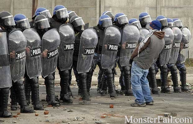 man pisses on a row of riot police
